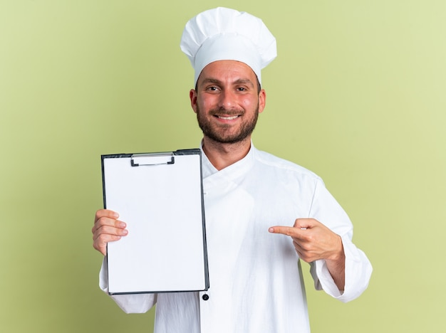 Glimlachend jonge blanke mannelijke kok in uniform van de chef-kok en pet tonen en wijzend op klembord