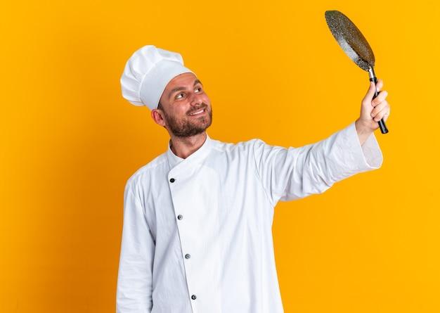Glimlachend jonge blanke mannelijke kok in uniform van de chef-kok en pet verhogen en kijken naar koekenpan geïsoleerd op oranje muur