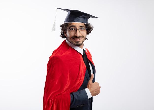 Glimlachend jonge blanke superheld man in optische bril dragen pak met rode mantel en afstuderen pet staat zijwaarts en duimen omhoog