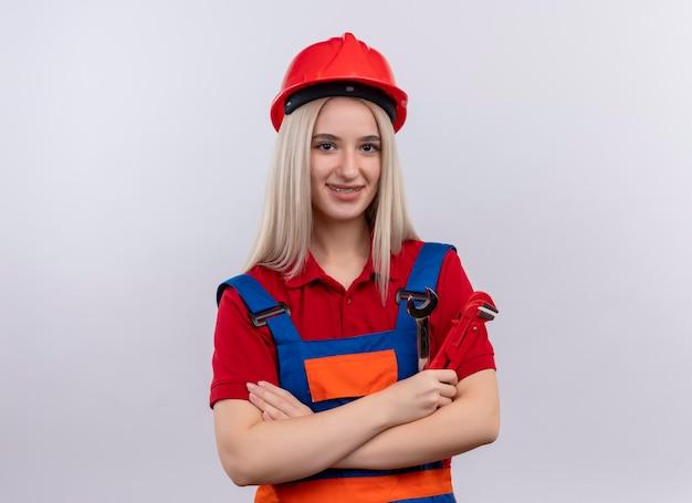 Glimlachend jonge blonde ingenieur bouwer meisje in uniform in tandheelkundige accolades met open uiteinde en waterpomptangen permanent met gesloten houding op geïsoleerde witte ruimte met kopie ruimte
