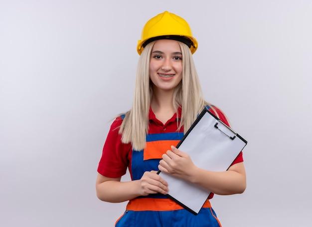 Glimlachend jonge blonde ingenieur bouwer meisje in uniform in tandheelkundige beugels klembord houden op geïsoleerde witte ruimte met kopie ruimte