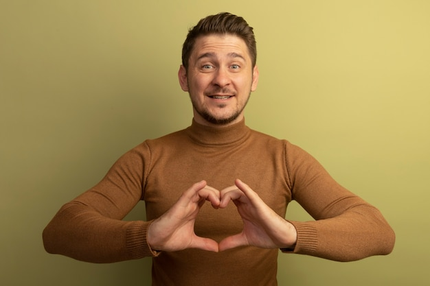 Glimlachend jonge blonde knappe man op zoek naar hart teken geïsoleerd op olijf groene muur