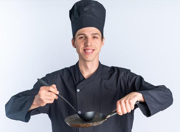 Glimlachend jonge blonde mannelijke kok in uniform van de chef-kok en pet kijken camera aanraken koekenpan met pollepel geïsoleerd op een witte muur