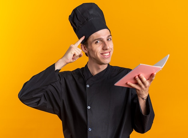 Glimlachend jonge blonde mannelijke kok in uniform van de chef-kok en pet met notitieblok kijken naar camera doen denk gebaar geïsoleerd op oranje muur