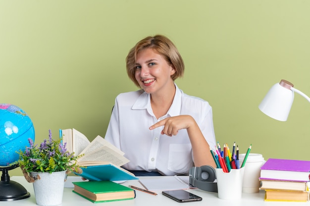 Glimlachend jonge blonde student meisje zit aan bureau met school tools houden open boek wijzend naar het kijken naar camera geïsoleerd op olijf groene muur