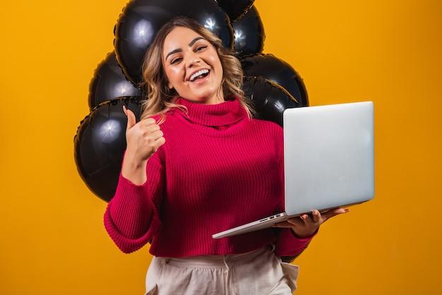 Glimlachend jonge brunette vrouw met pc laptopcomputer met leeg leeg scherm simuleren kopie ruimte op gele kleur achtergrond met lucht ballonnen studio portret. zwarte vrijdag verkoop