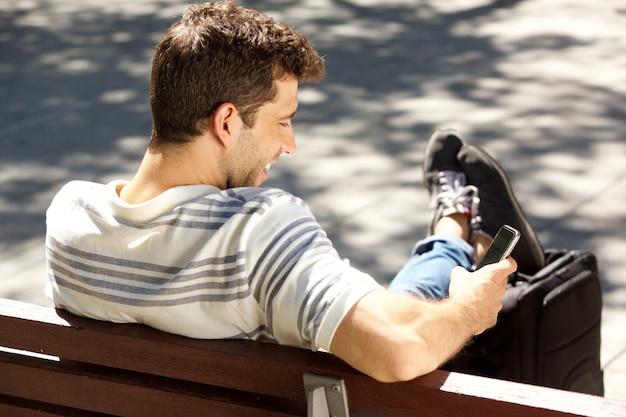 Glimlachend jonge man zittend op de bank buitenshuis met zak en het gebruik van slimme telefoon