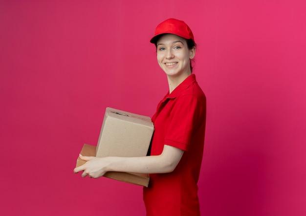 Glimlachend jonge mooie levering meisje dragen rode uniform en pet staande in profiel te bekijken met kartonnen doos en pizza pakket geïsoleerd op karmozijnrode achtergrond met kopie ruimte