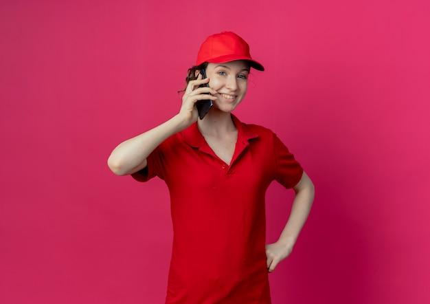 Glimlachend jonge mooie levering meisje in rood uniform en pet praten over telefoon hand zetten taille geïsoleerd op karmozijnrode achtergrond met kopie ruimte
