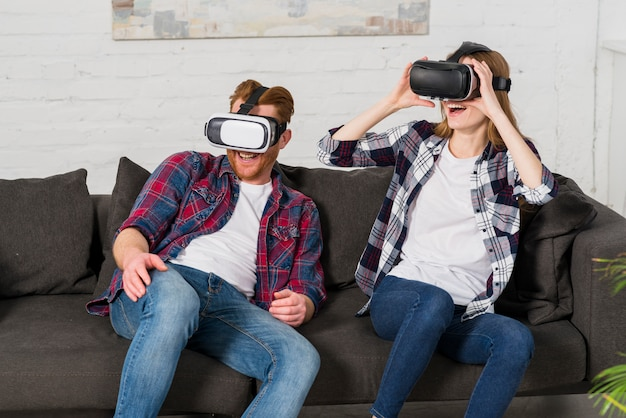Glimlachend jonge paar zittend op een zwarte bank met behulp van een vr headset thuis