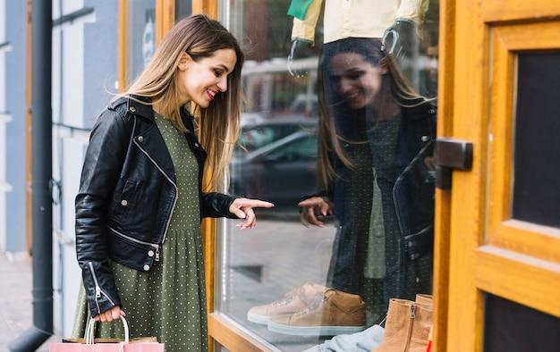 Glimlachend jonge vrouwelijke venster winkelen
