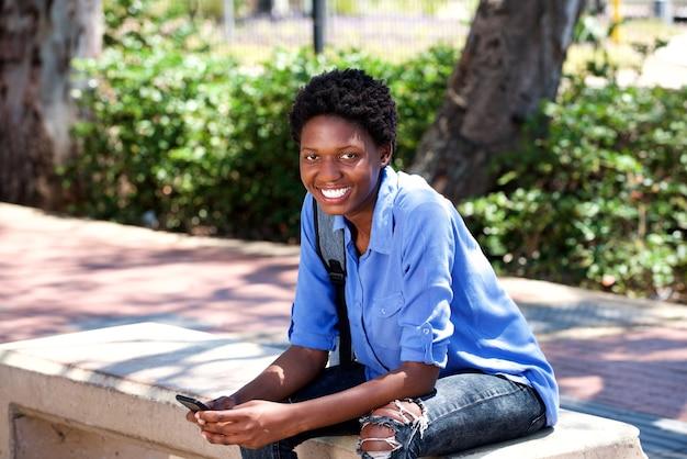Glimlachend jonge zwarte vrouw buiten zitten met een mobiele telefoon