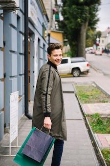 Glimlachend jongeman bedrijf boodschappentassen kijken over de schouder