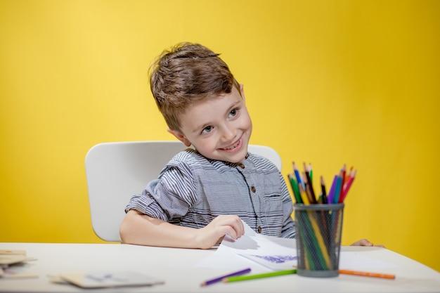 Glimlachend jongetje aan de tafel tekenen met kleurpotloden