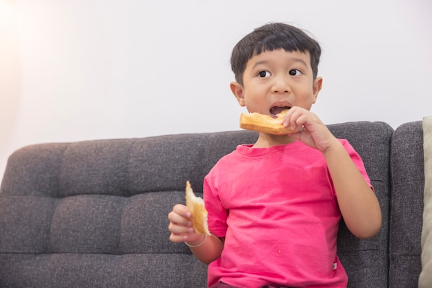 Glimlachend jongetje dat brood eet en tv kijkt op een comfortabele bank in de woonkamer