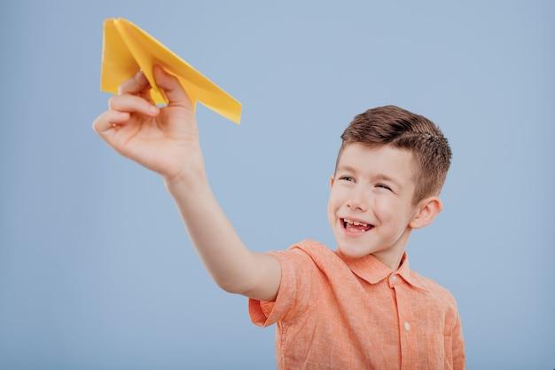 Glimlachend jongetje houdt geel papieren vliegtuigje in zijn hand geïsoleerd op blauwe achtergrond kopie ruimte