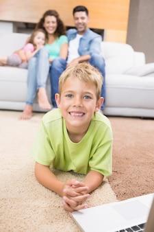 Glimlachend jongetje met behulp van laptop op het tapijt met ouders zitten bank