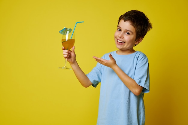 Glimlachend jongetje met een fruitcocktail op gele muur. kopieer ruimte