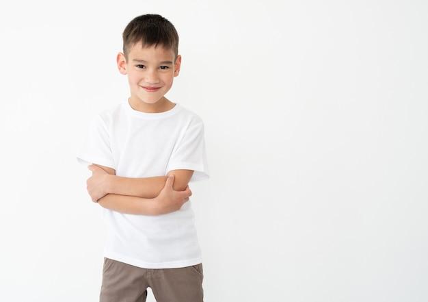 Glimlachend jongetje met gekruiste handen in witte tshirt