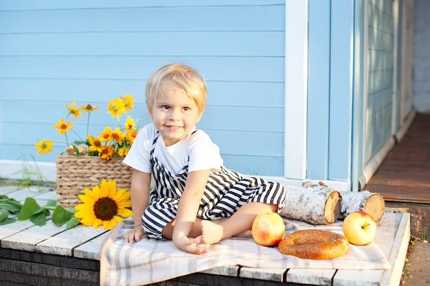 Glimlachend jongetje zittend op een houten veranda thuis kind speelt in de zomertuin