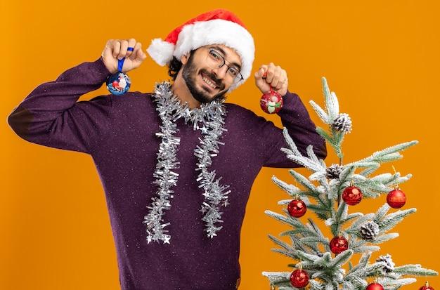 Glimlachend kantelend hoofd jonge knappe kerel die in de buurt van de kerstboom staat en een kerstmuts draagt met een slinger op de nek die kerstballen vasthoudt die op een oranje muur zijn geïsoleerd