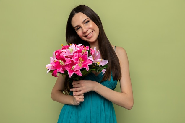 Glimlachend kantelend hoofd mooi jong meisje op gelukkige vrouwendag met boeket geïsoleerd op olijfgroene muur