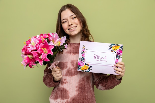 Glimlachend kantelend hoofd mooi jong meisje op gelukkige vrouwendag met boeket met ansichtkaart geïsoleerd op olijfgroene muur