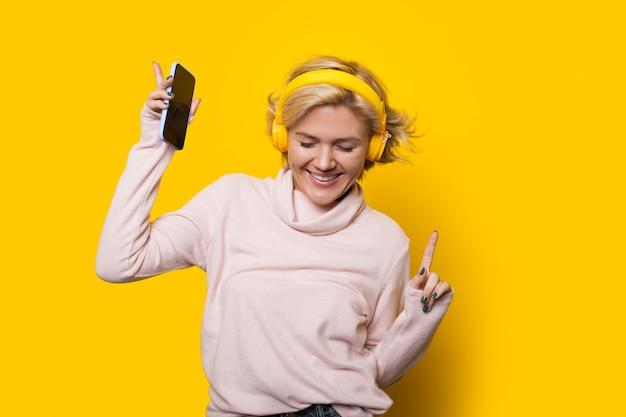 Glimlachend kaukasisch meisje met blond haar is dansen op een gele achtergrond terwijl u luistert naar muziek via een koptelefoon