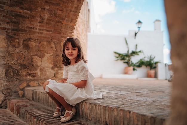 Glimlachend kaukasisch meisje met bruin haar, zittend op een stenen trap