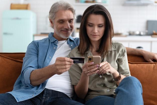 Glimlachend kaukasisch paar betrokken bij online winkelen, betalingsinformatie invoeren van creditcard in mobiele applicatie, tevreden met snelle geldoverdracht, modern tech concept.
