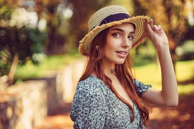 Glimlachend kaukasisch roodharig meisje in een wapperende jurk met strohoed die zich voordeed in de nazomer van het herfstpark