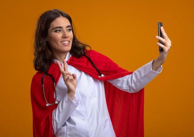 Glimlachend kaukasisch superheld meisje in uniform arts met rode cape en stethoscoop gebaren overwinning handteken