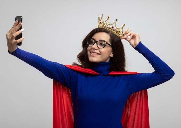 Glimlachend kaukasisch superheld meisje met rode cape in optische bril houdt kroon boven het hoofd