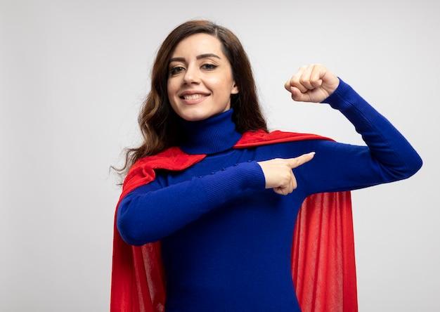 Glimlachend kaukasisch superheld meisje met rode cape tijden en punten op biceps op wit