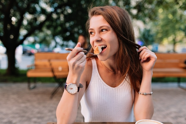 Glimlachend kaukasisch vrouwelijk model buitensporige cupcake eten in de zomercafetaria buiten