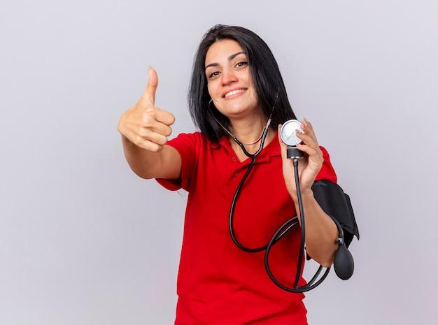 Glimlachend kaukasisch ziek meisje dragen stethoscoop kijken camera haar druk meten met bloeddrukmeter weergegeven: duim omhoog geïsoleerd op een witte achtergrond met kopie ruimte