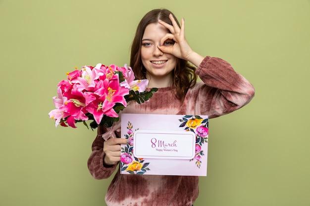 Glimlachend kijken gebaar mooi jong meisje op gelukkige vrouwendag met boeket met ansichtkaart geïsoleerd op olijfgroene muur