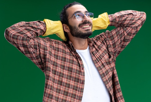 Glimlachend kijken naar kant jonge knappe schoonmaakster met t-shirt en handschoenen handen achter het hoofd zetten geïsoleerd op groene muur