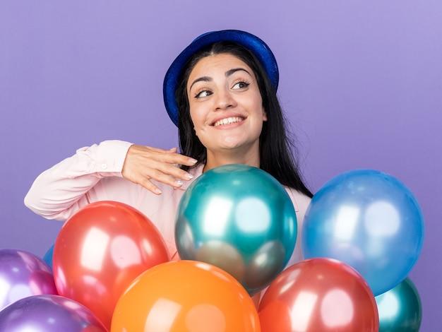 Glimlachend kijkend jong mooi meisje met een feesthoed die achter ballonnen staat