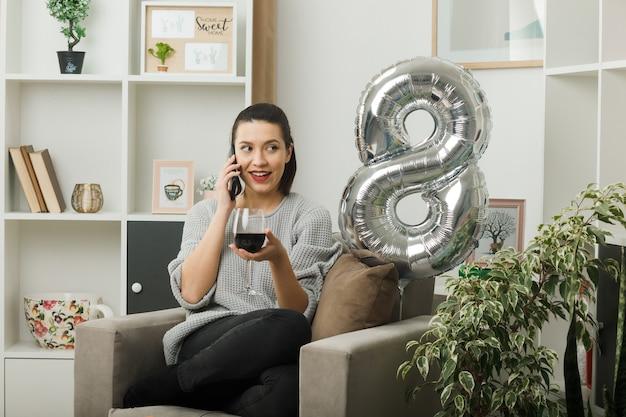 Glimlachend kijkend mooi meisje op een gelukkige vrouwendag met een glas wijn spreekt over wijn zittend op een fauteuil in de woonkamer
