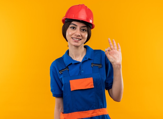 Glimlachend kijkend naar camera jonge bouwer vrouw in uniform met goed gebaar