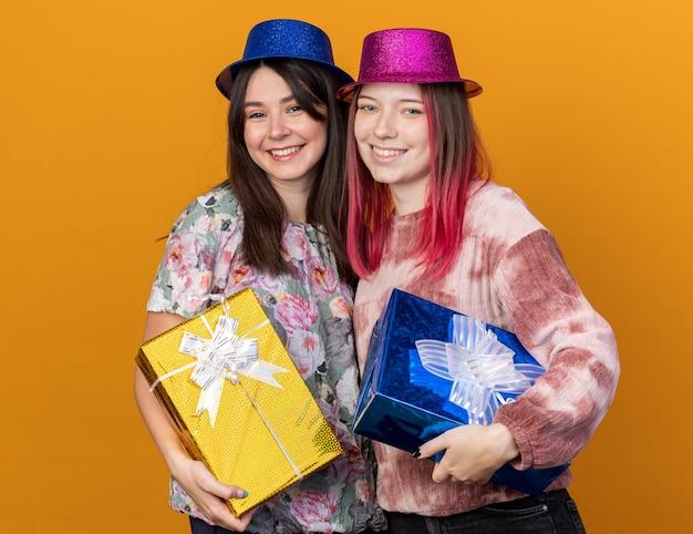 Glimlachend kijkend naar camerameisjes die een feestmuts dragen met geschenkdozen
