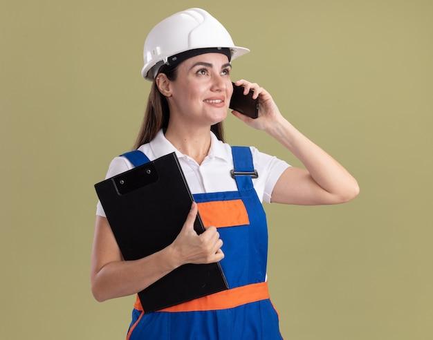 Glimlachend kijkend naar de jonge bouwvrouw aan de zijkant in uniform met klembord spreekt op telefoon geïsoleerd op olijfgroene muur