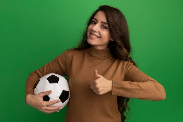 Glimlachend kijkend naar de voorste jonge mooie bal van de meisjesholding en het tonen van duim omhoog geïsoleerd op groene muur