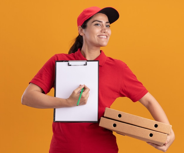 Glimlachend kijkend naar een jong bezorgmeisje aan de zijkant, gekleed in uniform en pet met klembord met pizzadozen geïsoleerd op een oranje muur