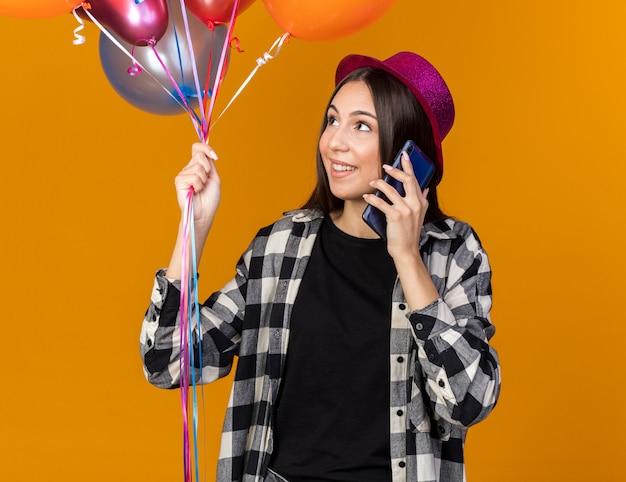 Glimlachend kijkend naar een jonge, mooie vrouw die een feesthoed draagt en ballonnen vasthoudt, spreekt op de telefoon geïsoleerd op een oranje muur