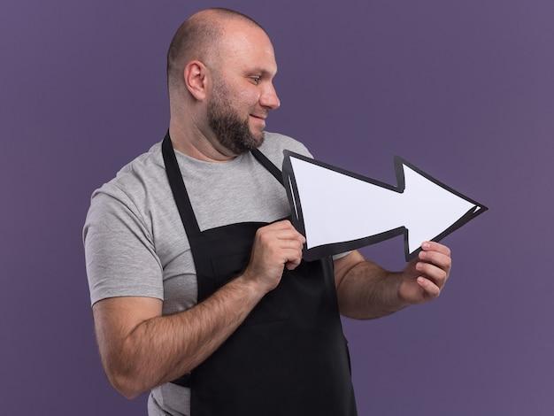 Glimlachend kijkend naar een mannelijke kapper van middelbare leeftijd in een uniforme houdrichtingmarkering geïsoleerd op een paarse muur