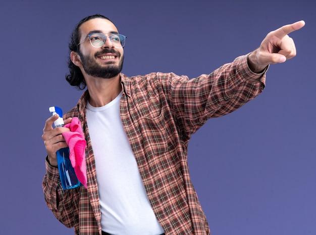 Glimlachend kijkend naar kant jonge knappe schoonmaakster die t-shirt draagt ?? die de spuitfles met voddenpunten aan kant draagt die op blauwe muur wordt geïsoleerd