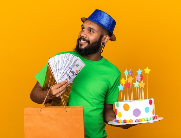 Glimlachend kijkende jonge afro-amerikaanse man met een feestmuts met geschenken en cake met contant geld