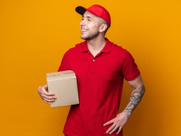 Glimlachend kijkende jonge bezorger die een uniform draagt met een dop die een doos vasthoudt en de hand op de heup legt